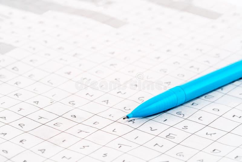 Czas wolny aktywność Zakończenie błękitny pióro na gazetowej crossword łamigłówce z listami zdjęcia stock