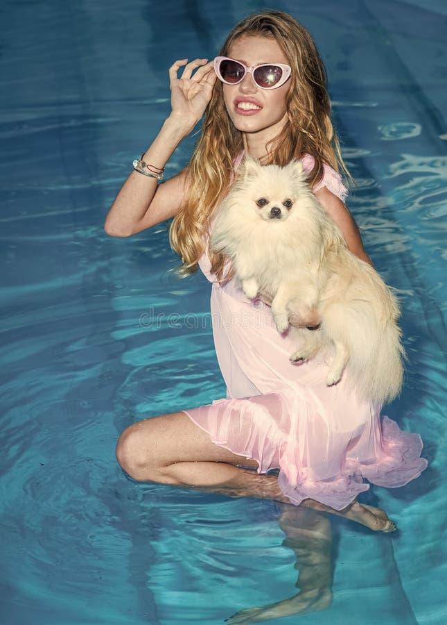 Czas wolny przy morzem Dziewczyna z małym psem w pływackim basenie obraz stock