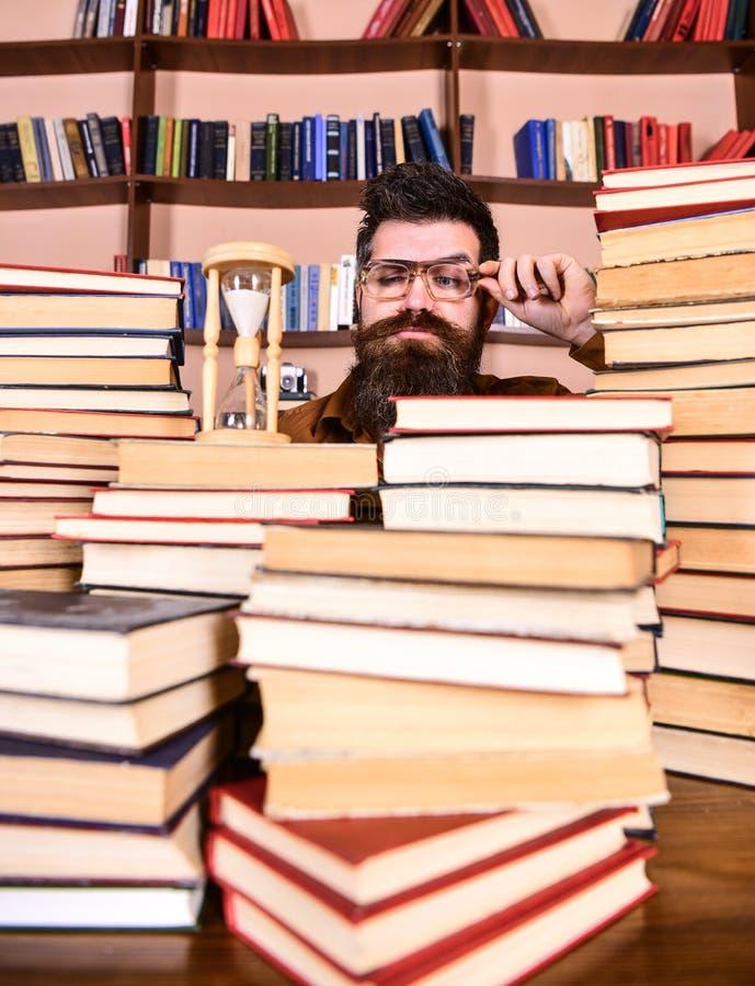 Czasu Spływowy pojęcie Nauczyciel lub uczeń z brody studiowaniem w bibliotece Mężczyzna na poważnym twarzy dopatrywania czasie iś obraz royalty free