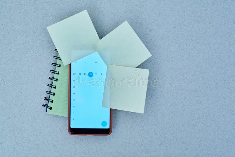 Czasu zarządzania ostateczny termin i rozkładu pojęcie: kalendarz na smartphone majcherach i ekranie zdjęcie royalty free