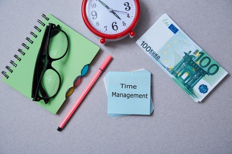 Czasu zarządzania ostateczny termin i rozkładu pojęcie: zegar, notatnik i sterta rachunki na popielatym tle, Mieszkanie nieatutow zdjęcia stock