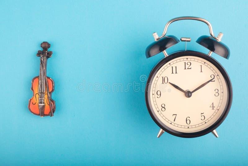 Czasu zarządzania pojęcie, budzik i skrzypce na błękitnym tle, obraz royalty free