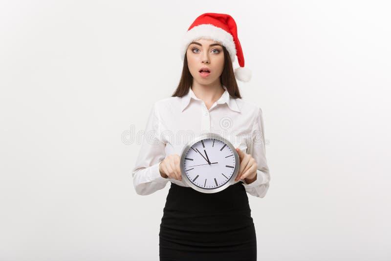 Czasu zarządzania pojęcie - Młoda biznesowa kobieta trzyma zegar odizolowywający nad białym tłem z Santa kapeluszem fotografia stock