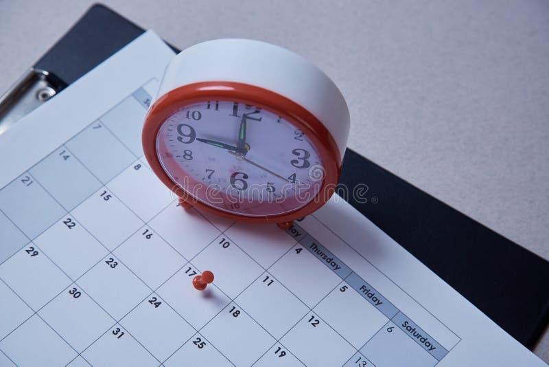Czasu zarządzanie, ostateczny termin i rozkładu pojęcie: budzik i pushpin na rozkładu planie zdjęcia royalty free