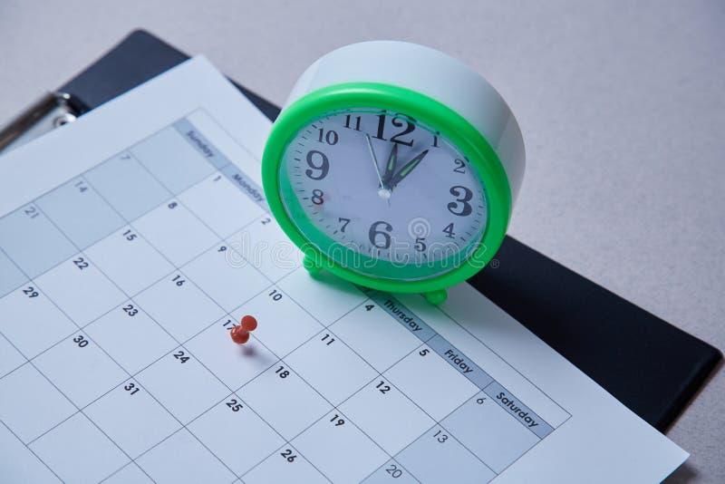 Czasu zarządzanie, ostateczny termin i rozkładu pojęcie: budzik i pushpin na rozkładu planie zdjęcie royalty free