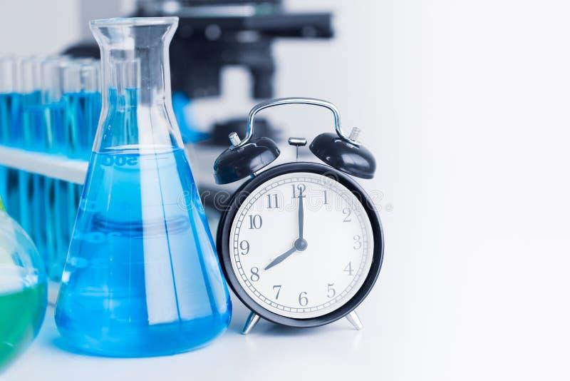 Czasu zegar z Chemicznej nauki badaniem w laboratorium zdjęcia stock