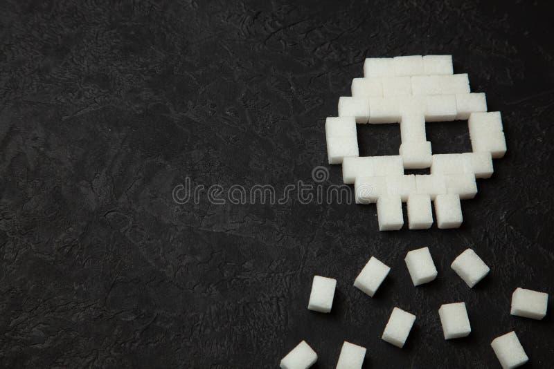 Czaszka od białego cukieru sześcianów na czarnym tle Cukierów zwłoka i udział szybki ulevodov szkodliwi ciało  zdjęcia stock