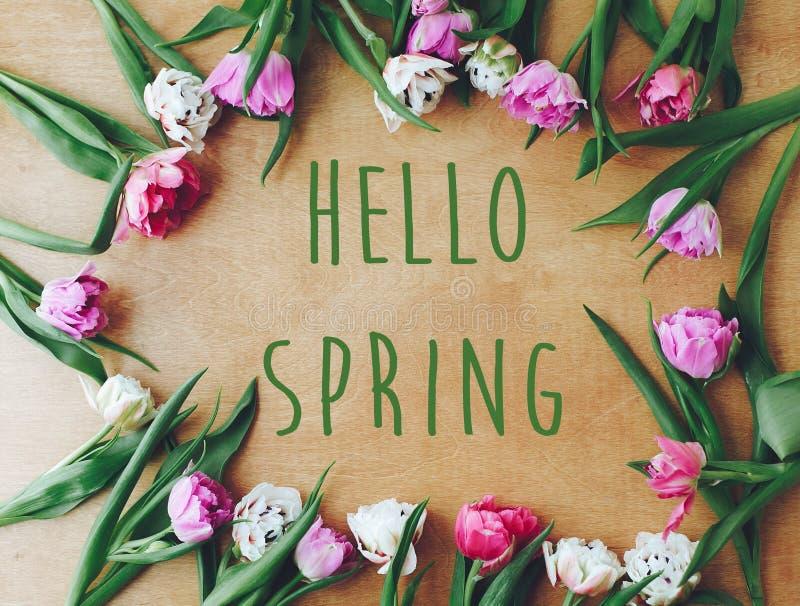 Cześć wiosna teksta znak na pięknych dwoistych peonia tulipanów ramowym mieszkaniu kłaść na drewnianym stole Wiosna Elegancka kwi zdjęcia royalty free