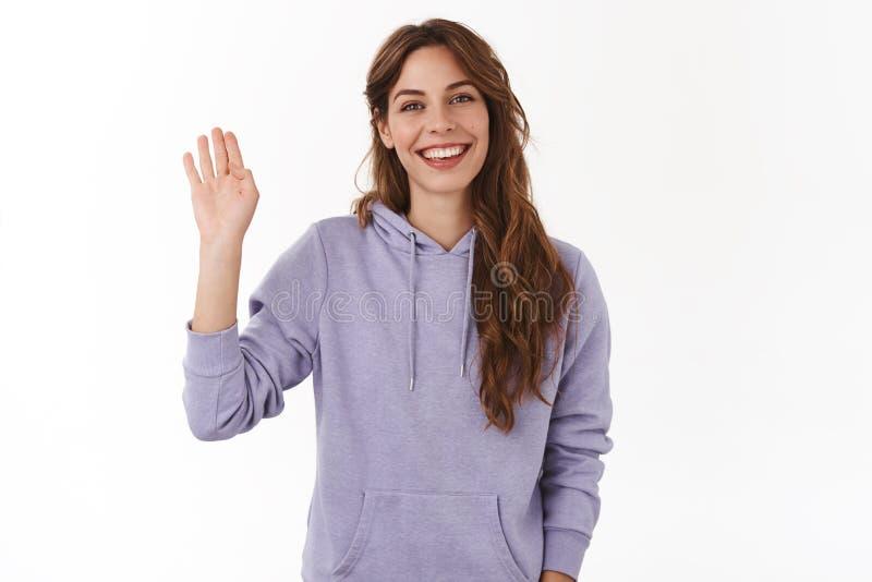 Cześć internet Rozochocony charyzmatyczny atrakcyjny życzliwy falowanie podnoszę dziewczyny ręki powitania gesta ono uśmiecha się zdjęcia stock
