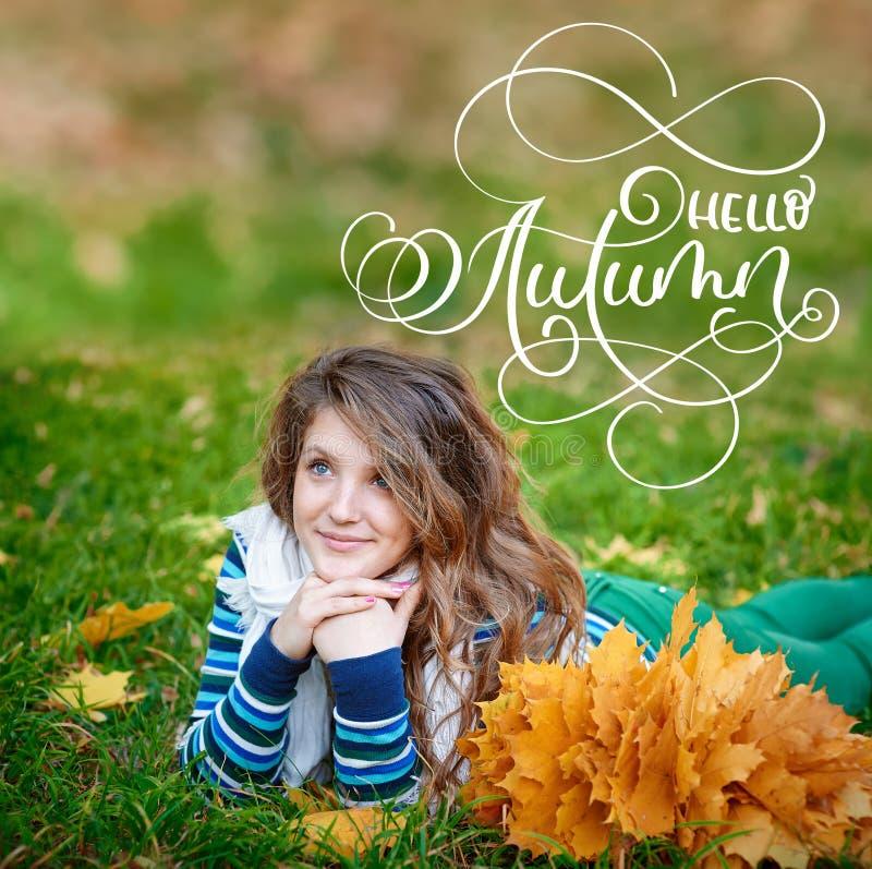 Cześć jesieni kaligrafii literowania tekst Młoda piękna dziewczyna w jesień parku z wiankiem kolor żółty opuszcza na głowie obrazy royalty free