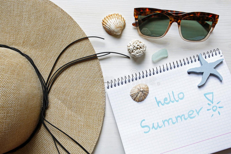 Cześć lata pojęcia słomiany kapelusz, seashells, okulary przeciwsłoneczni i notatnik, obraz stock