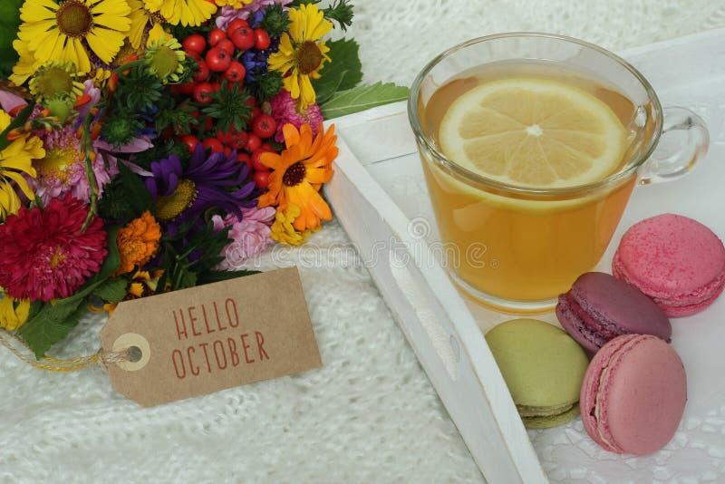 Cześć Października tekst na etykietce, jesień kwiatach i filiżance herbata, zdjęcie royalty free