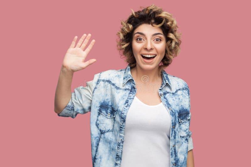 Cze?? Portret zdziwiona szczęśliwa młoda kobieta z kędzierzawą fryzurą w przypadkowej błękitnej koszulowej pozycji, powitanie, fa obrazy stock