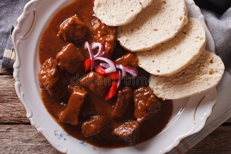 Czech cuisine: beef goulash with Knodel macro. horizontal top vi. Czech cuisine: beef goulash with Knodel macro on a plate. horizontal view from above stock photo