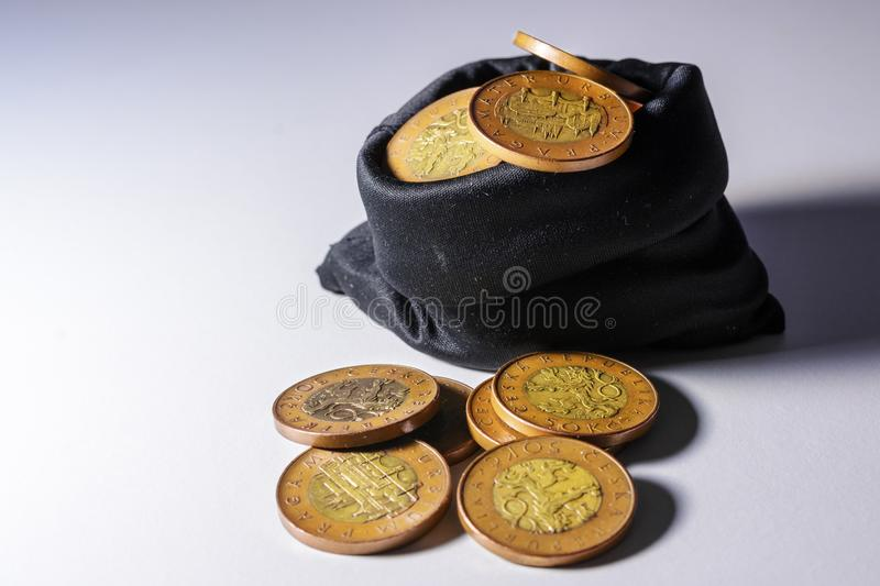 Czech gold coins in a black bag on a white background royalty free stock images