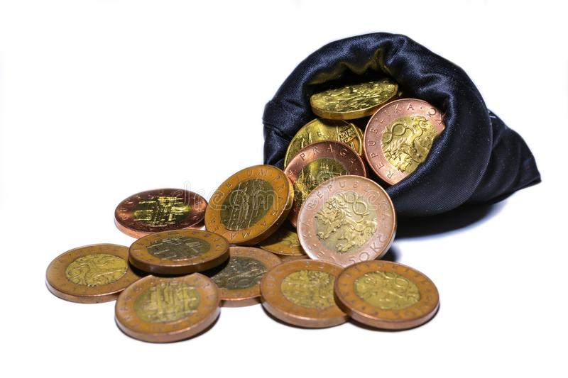 Czech gold coins in a black bag on a white background royalty free stock photos