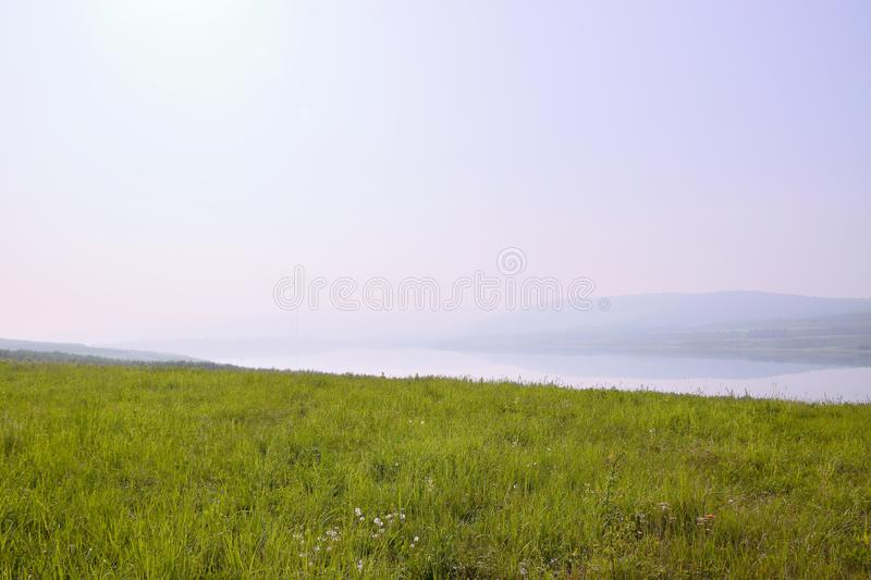 Czech landscape with meadow, new lake named Milada and mountains in foggy morning stock image
