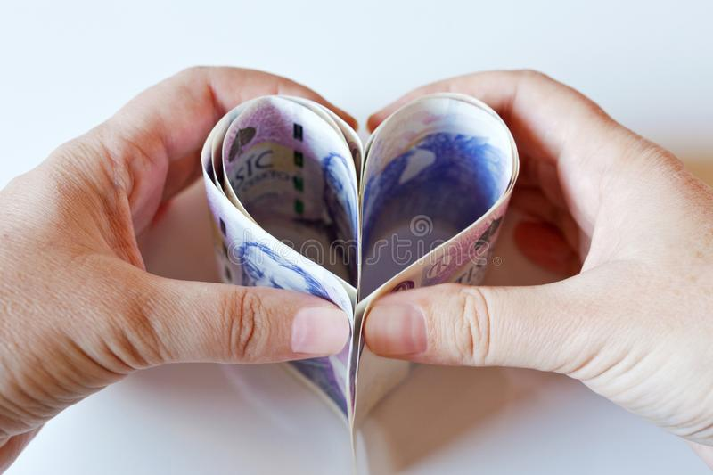 Czech paper money in a shape of the heart with hands - economy royalty free stock photography