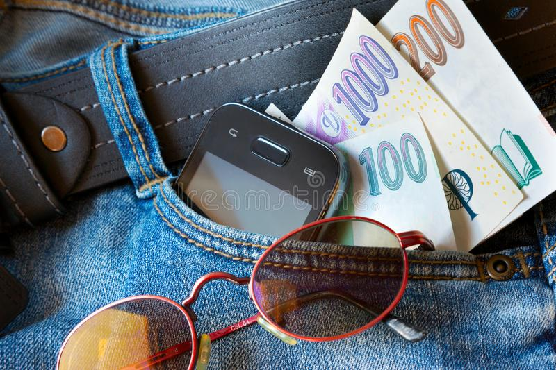Czech personal belongings from the trousers pocket. Purse, paper money, sun glasses and mobile phone royalty free stock photos