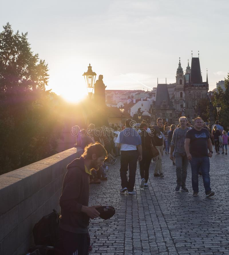 Czech Republic, Prague , September 8, 2018: Young man begging on Charles Bridge on Mala Strana Bridge Tower with walking tourist p. Eople and souvenir sellers at royalty free stock photography