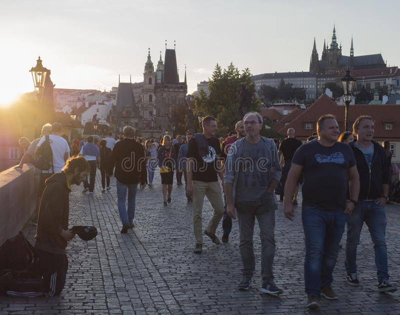 Czech Republic, Prague , September 8, 2018: Young man begging on Charles Bridge on Mala Strana Bridge Tower with walking tourist p. Eople at sunset, lense flare royalty free stock image