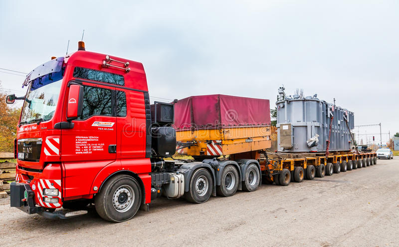 CZECH REPUBLIC, PRESTICE, 11 NOVEMBER, 2014:Transport of heavy, oversized loads and construction machinery. Red car stock photo