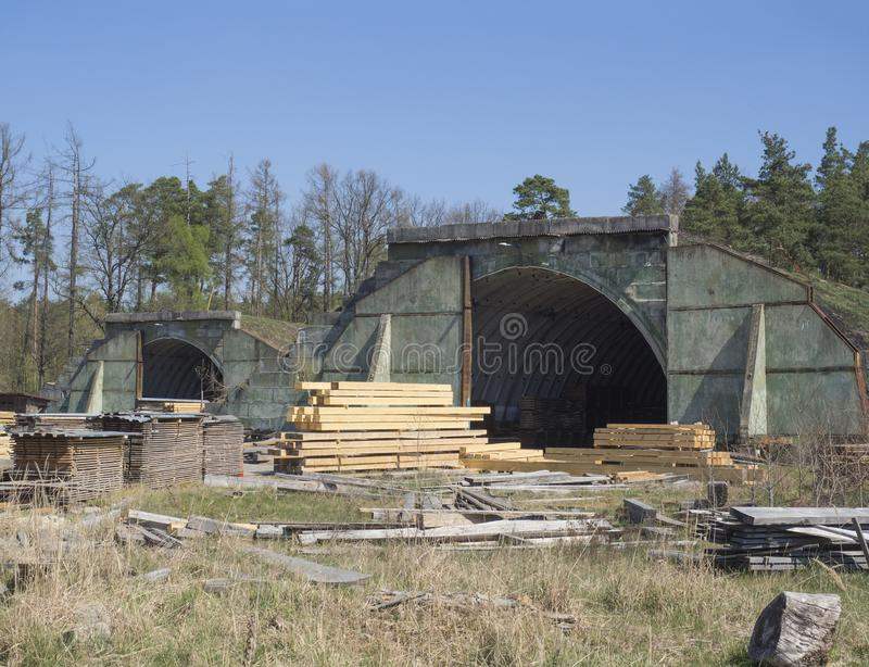 Czech Republic, Ralsko, April 26, 2019: former Soviet army concrete hangar shelter, serving as lumber mill on airport at stock images