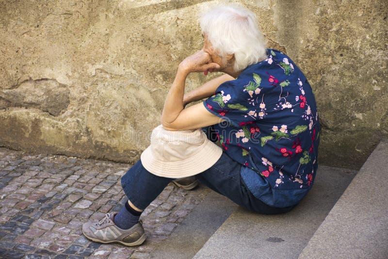 Czechia老妇人坐偏僻在布拉格城堡路  库存图片