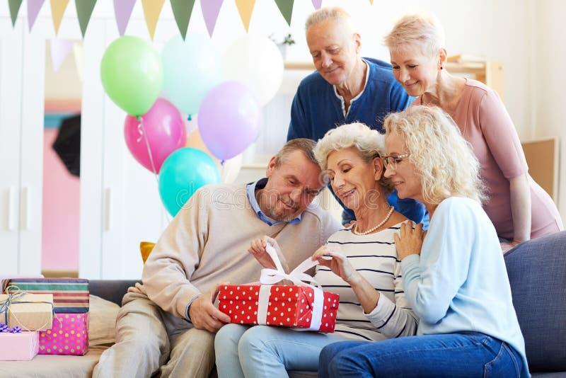 Czekać gdy urodzinowa kobieta otwiera prezent zdjęcia stock
