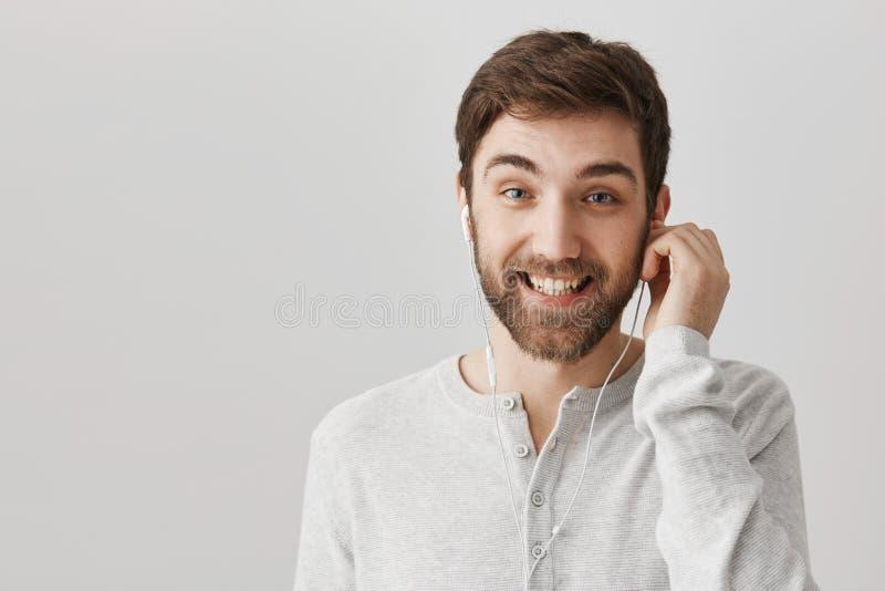 Czeka mój ulubioną piosenkę przychodzi Portret atrakcyjnego rozochoconego caucasian chłopaka słuchająca muzyka w słuchawkach i obraz stock