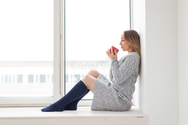 Czekania, samotności i piękna pojęcie, - młoda kobieta w wełny sukni z filiżanką gorący herbaciany obsiadanie na windowsill zdjęcia royalty free