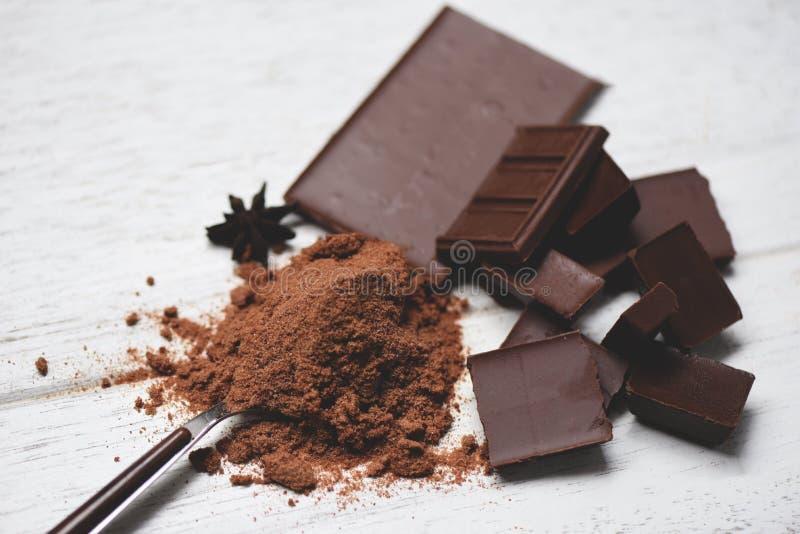 Czekolada i przyprawa na tle stołowym / kawałki czekolady, proszek na łyżce słodki deser do przekąsek obraz royalty free