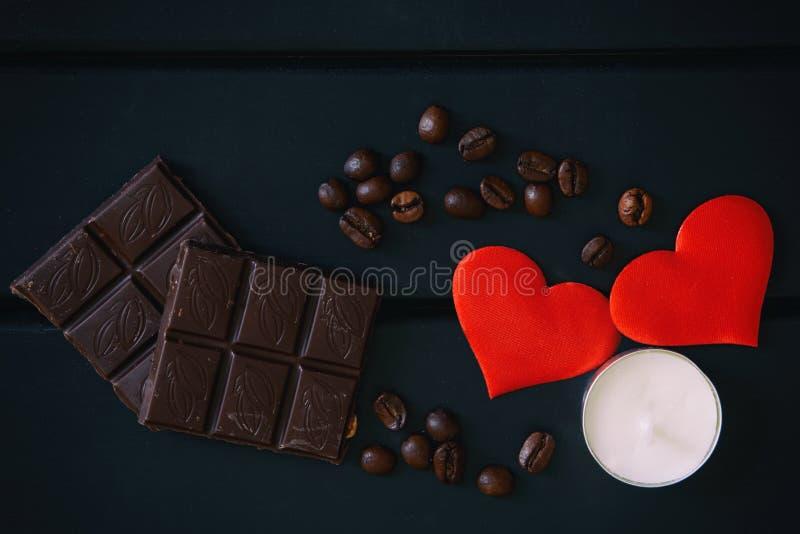 Czekolada, kawowe fasole, świeczka i czerwieni serca, kłamamy na czarnym drewnianym tle Wciąż życie dla kochanków obraz royalty free