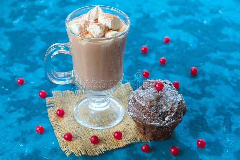 Czekoladowa babeczka czekoladowa ozdobiona czerwonymi jagodami i szklanką gorącego kakao na niebieskim tle Koncepcja t fotografia royalty free