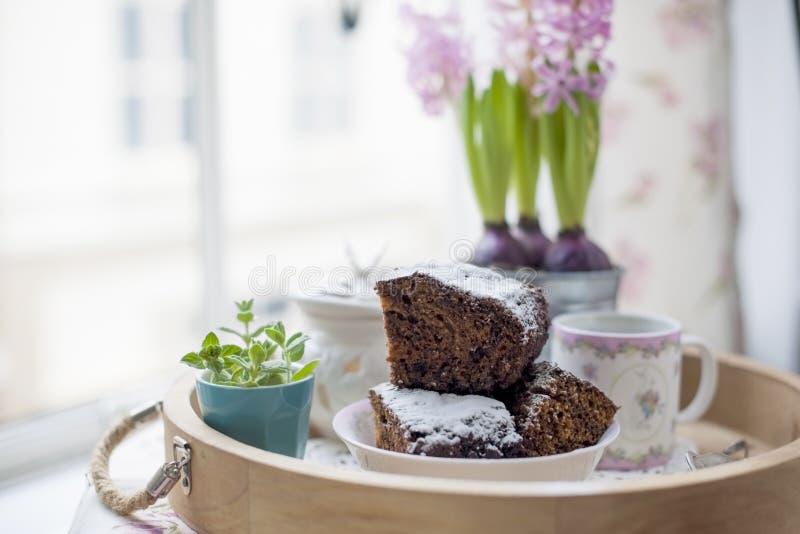 Czekoladowa babeczka z cukierem i kawą Śniadanie na drewnianej tacy i kwiatach Widok od okno miasto zdjęcie royalty free