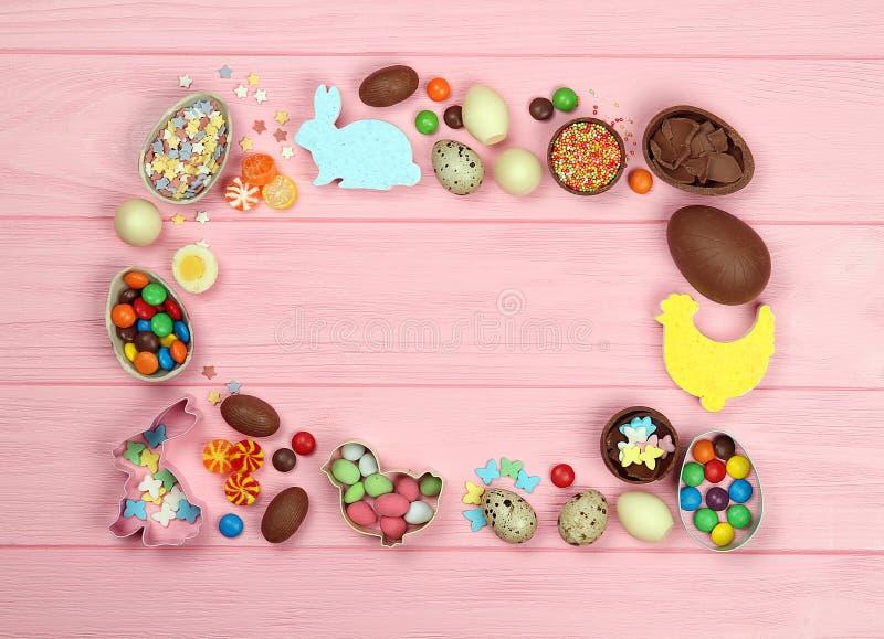 Czekoladowa Easter cukierków i jajek rama na różowym tle zdjęcie royalty free