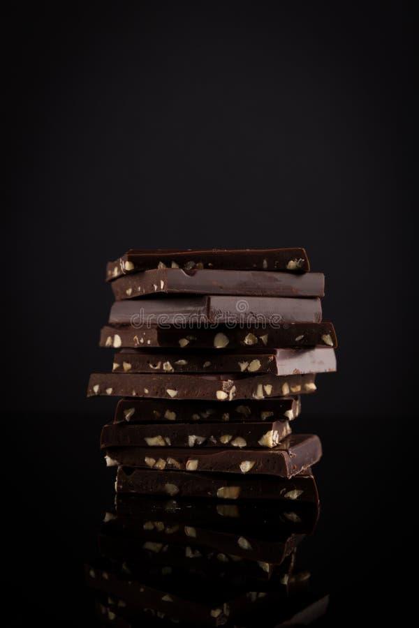 Czekoladowa sterta Hazelnut czekolady Ciemny stos odizolowywający na czarnym tle obraz royalty free