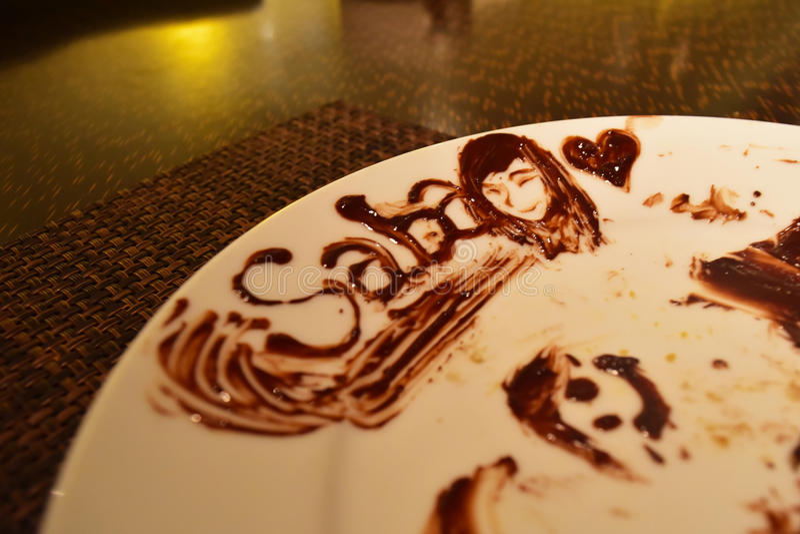 Czekoladowa sztuka na talerzu - Saba Malezja z dziewczyny uśmiechniętą twarzą i sercem zdjęcia royalty free