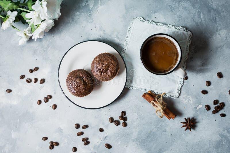 Czekoladowe babeczki z filiżanką gorąca czarna kawa na cocrete tle obrazy royalty free