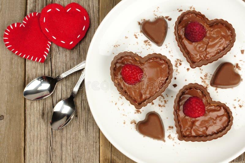 Czekoladowe kierowe deserowe filiżanki z puddingiem i malinkami fotografia stock