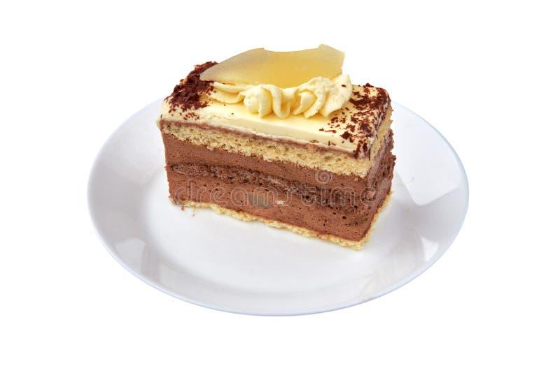 Czekoladowego mousse tort z śmietanką, cacao, bonkretą i migdałem na białej porcelanie z białym tłem, z bliska zdjęcia royalty free