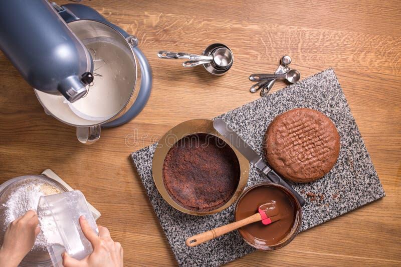 Czekoladowego torta wypiekowi składniki na kuchennym stole z kitchenware, odgórny widok zdjęcie royalty free