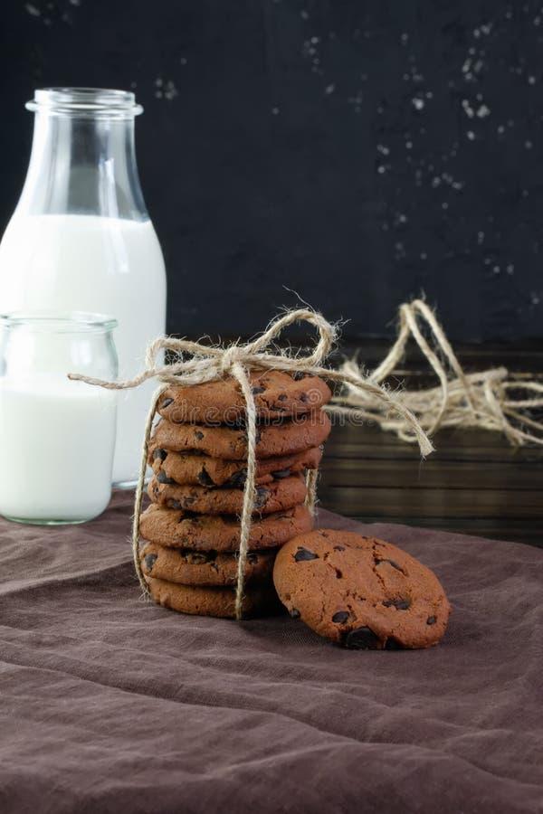 Czekoladowego układu scalonego ciastka na ciemnym tle z mlekiem zdjęcie royalty free