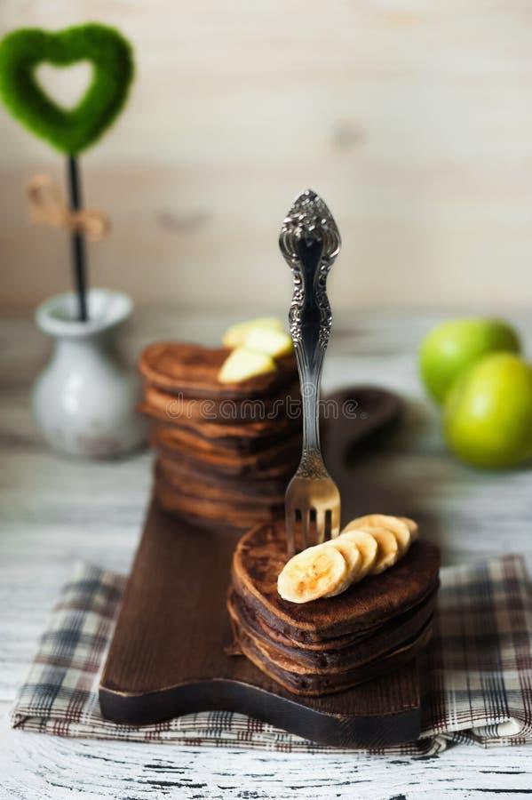 Czekoladowi bliny w formie serca z siekającymi bananowymi plasterkami na textured drewnianej desce Blinu zakończenie obrazy stock