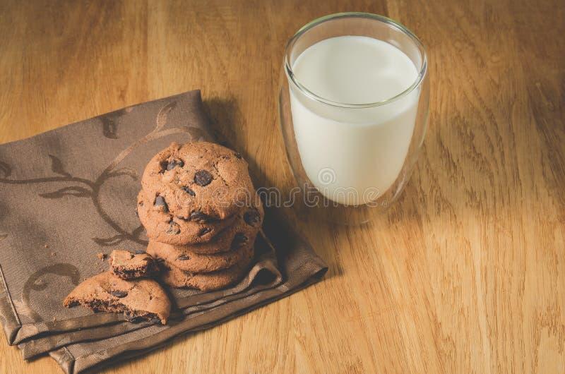 Czekoladowi ciastka, szk?o mleko na i szk?o mleko na drewnianym stole drewnianych sto?owych, Czekoladowych ciastkach/ Selekcyjna  fotografia stock