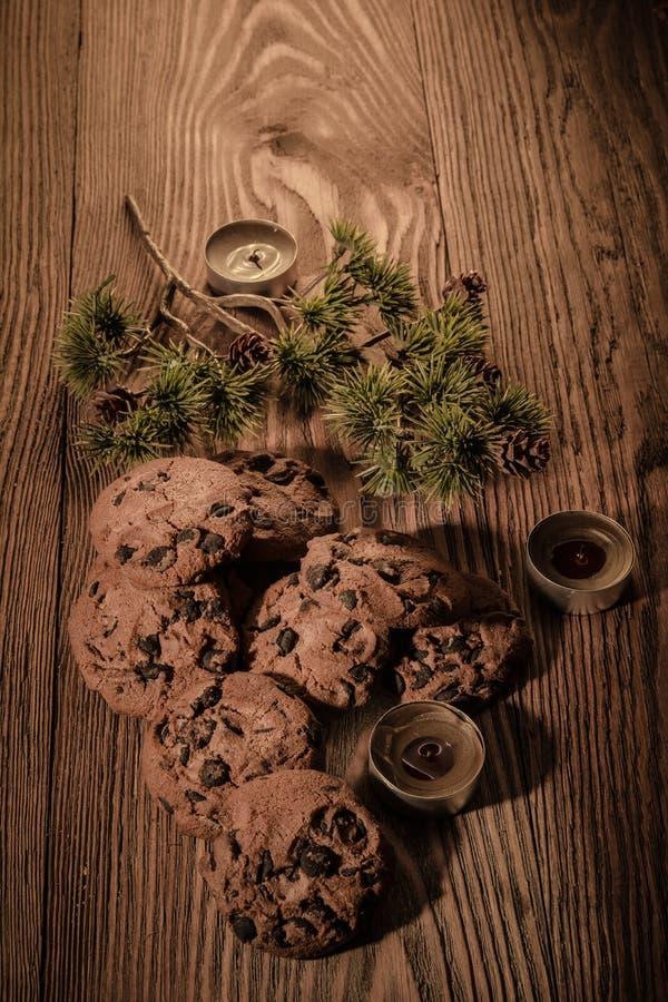 Czekoladowi ciastka z jedlinowymi gałąź na drewnianym tle z świeczkami 1 fotografia royalty free