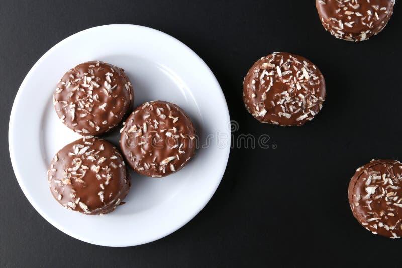 Czekoladowi ciastka z kokosowego golenia czekoladowym narzutem i koksem na drewnianym czarnym tle obraz royalty free