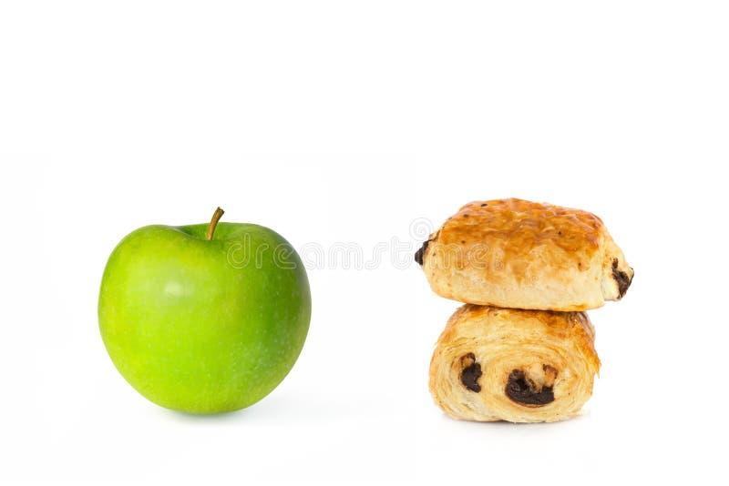Czekoladowi croissants i zielony jabłko na białym tła, zdrowego lub niezdrowego karmowym wyborze, zdjęcie stock