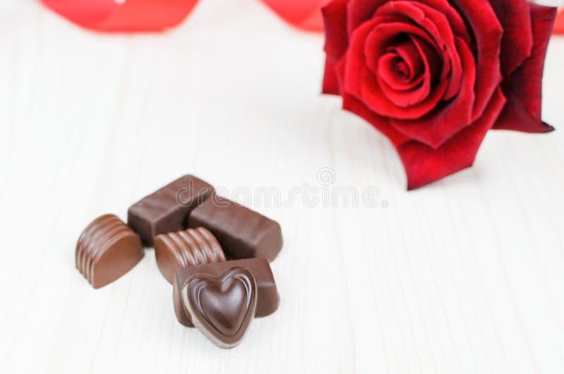 Czekoladowi cukierki i czerwieni róża fotografia royalty free