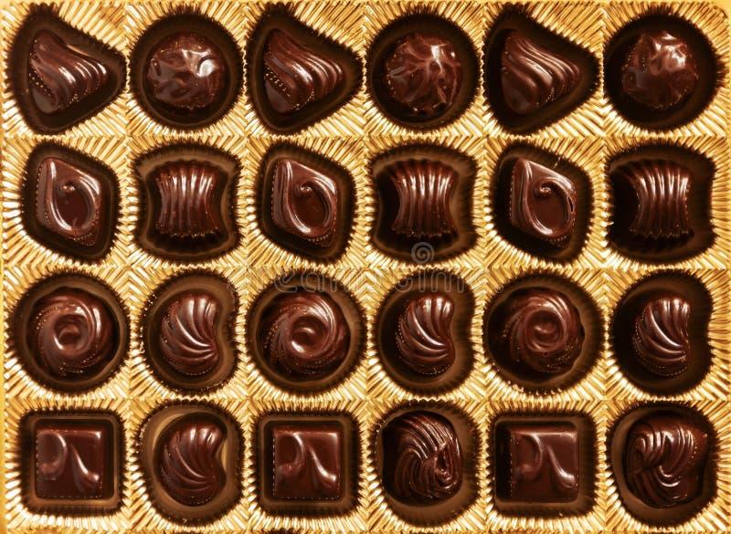Czekoladowi cukierki różni kształty w złota pudełku, odgórny widok, s fotografia stock